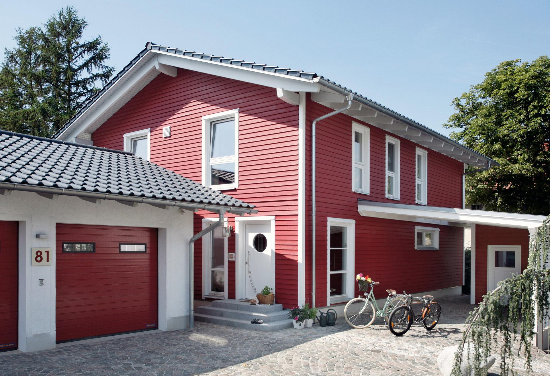 Prefabricated house with red wooden facade and double garage