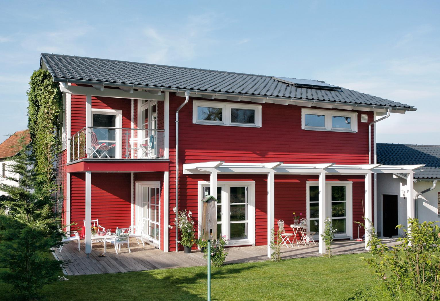 Detached house with red wooden facade in country style